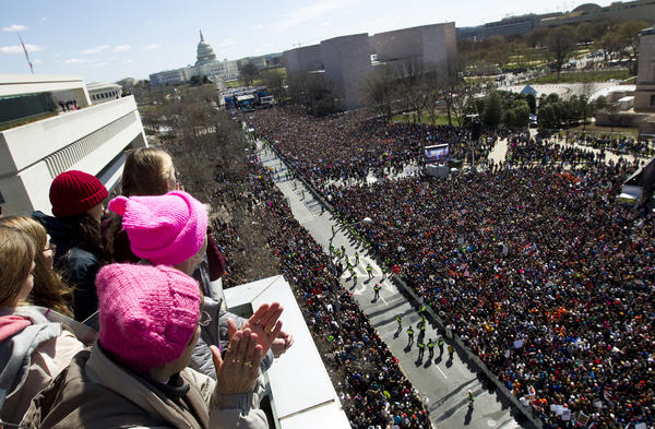 People on the balcony at the Newseum cheer the protesters on Pennsylvania Avenue as they look toward the stage near the Capitol in Washington.
