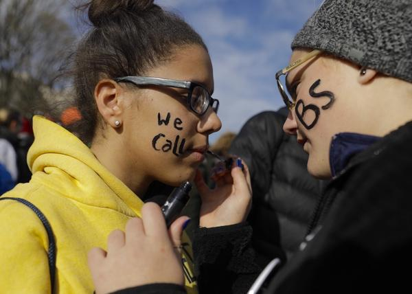 "Abby Keller, 15, uses black lipstick to write ""we call BS"" on 15-year-old Kendra Walker's face. They are both from Fauquier County, Va."