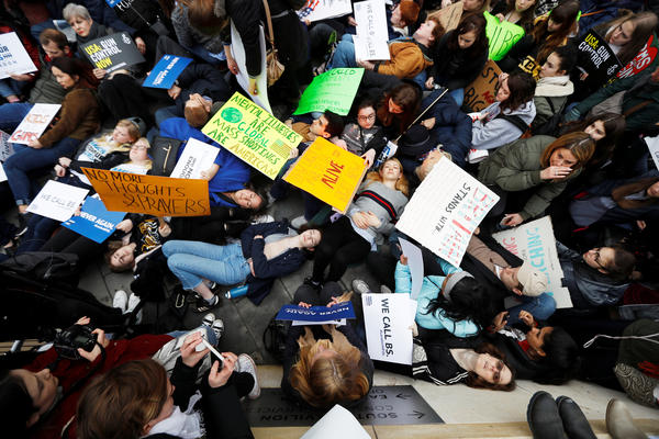 "Protesters stage a ""die-in"" during a demonstration in favor of tighter gun control in the United States, outside the U.S. Embassy in London."