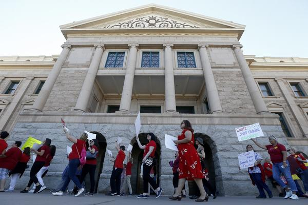 Arizona teachers and education advocates march in front of the Arizona Capitol highlighting low teacher pay and school funding in Phoenix.