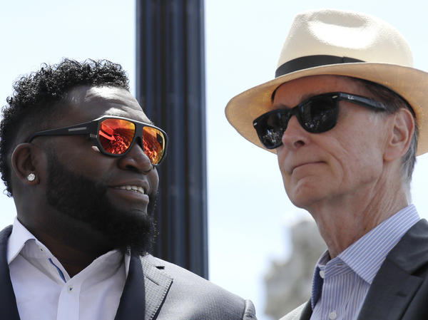 Retired Boston Red Sox designated hitter David Ortiz, left, stands with team principal owner John Henry while honored with the renaming of a portion of Yawkey Way to David Ortiz Drive outside Fenway Park in Boston on June 22, 2017. Henry says he wants to rename all of Yawkey Way, a street that has been an enduring reminder of the franchise's complicated racial past.