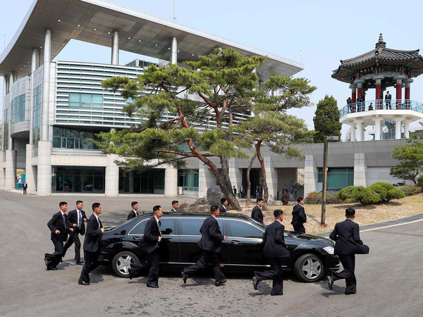 North Korean security officers jog alongside the vehicle carrying Kim as he left for a lunch break after the morning session of his summit meeting with Moon.