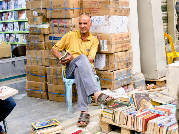 "Shalan Zeidan sits next to his books for sale. He has been selling books on al-Mutanabi street for 20 years. He says Iraq has no real government and he won't vote. ""They are tribes. We are ruled by tribes."""