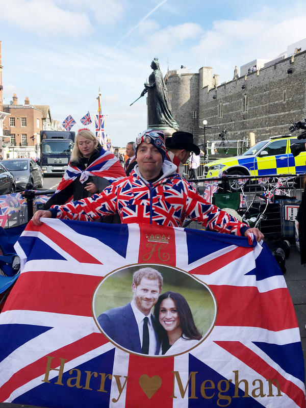 Royal super-fan John Loughrey, 63, poses in front of a statue of Queen Victoria with Windsor Castle behind.