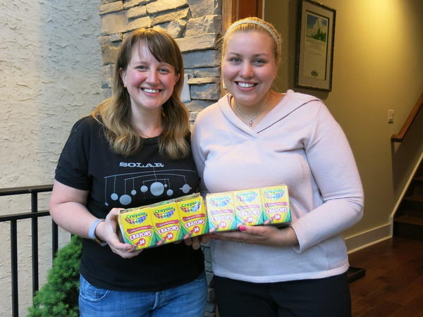 Johanna Humphrey, left, ended up with 24 boxes of crayons she didn't need. She gave them to teacher Laura Smith, right, through the Buy Nothing Project. It encourages people to share without money changing hands.