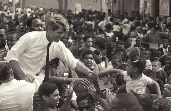 Robert F. Kennedy stands in an open-top convertible and shakes hands with members of a crowd as he campaigns for the democratic Presidential nomination in Detroit on May 15, 1968.