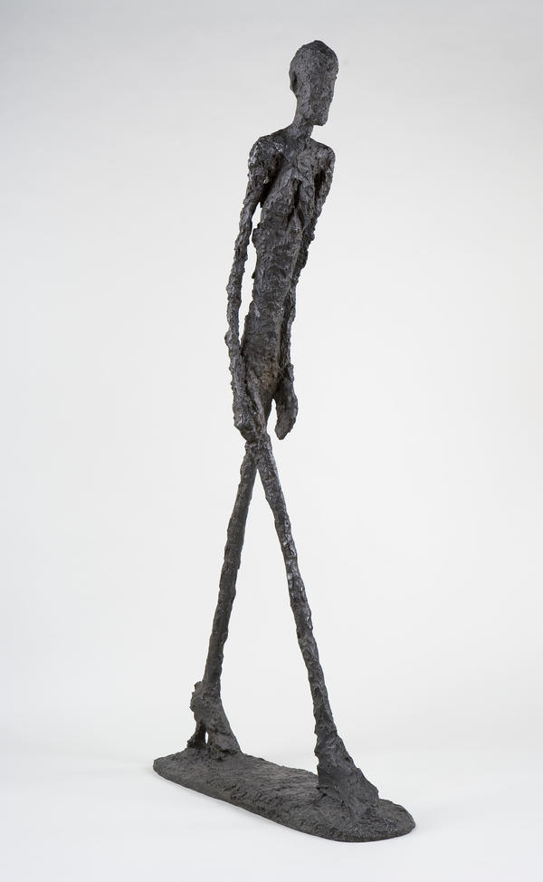Giacometti's impossibly thin bronze bodies stride like shadows. Above, his 1960 sculpture <em>Walking Man I </em>(<em>Homme qui marche I</em>).