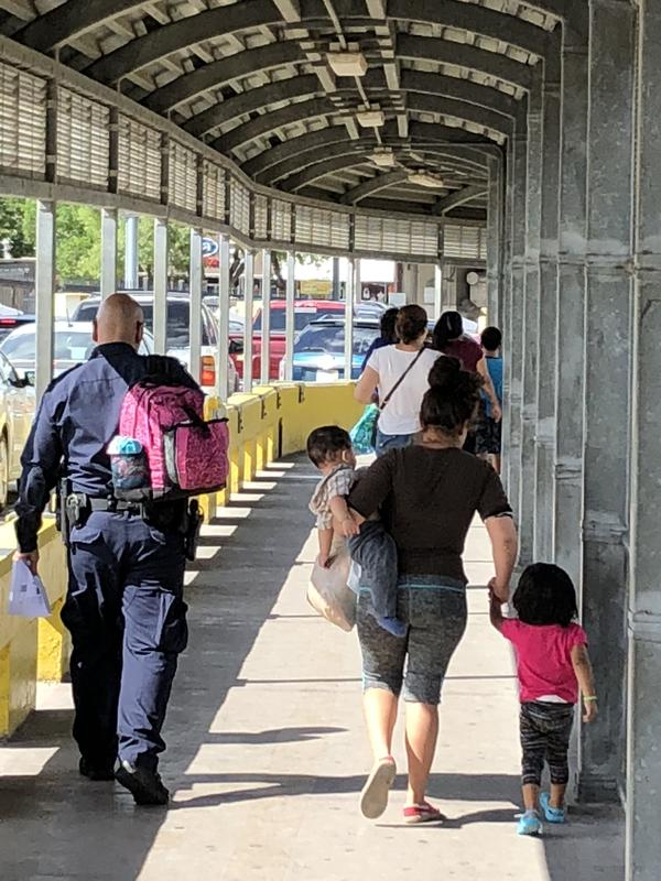 Victor Berduo's daughter-in-law, Yeni Johary Leal Cruz and her two small children are escorted by an agent as they cross the bridge into Brownsville, Texas. They were the only family members to enter America.