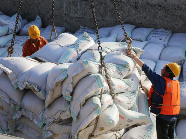 Workers transfer bags of soybean meal at a port in Nantong in China's eastern Jiangsu province.
