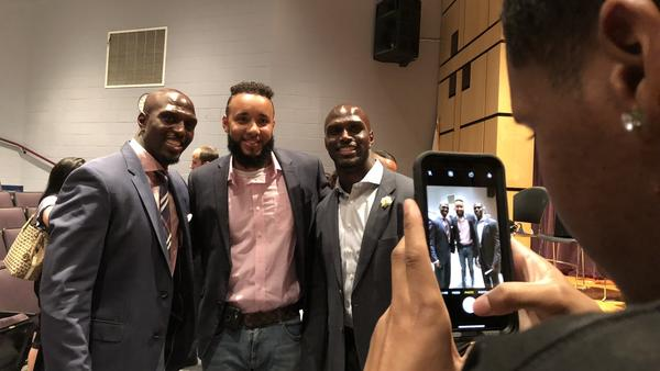 New England Patriots players Devin McCourty, left, and Jason McCourty, far right, post for a photo Tuesday night at the Suffolk County DA candidates' panel.