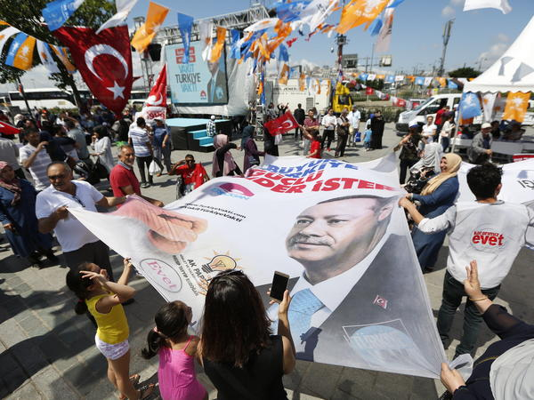 People wave a banner showing Turkey's President Recep Tayyip Erdogan during a gathering of supporters of his ruling Justice and Development Party (AKP) in Istanbul.