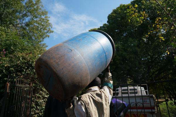 Enyway Chatambudza, 33, carries a container to fill with water on the way to plant flowers in Harare.