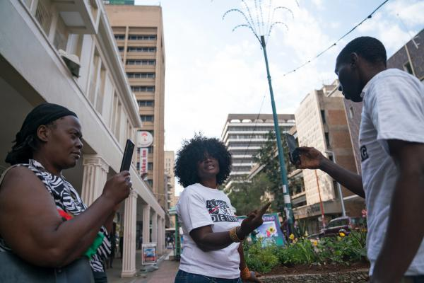 Savanna Madamombe's sister Christina (left) and Kuda Ndanga (right) record a video of Savanna while she is planting flowers in downtown Harare.