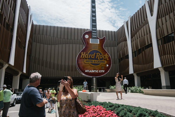 Visitors pose in front of the new Hard Rock Hotel and Casino on its opening day in Atlantic City,N.J. on Thursday.