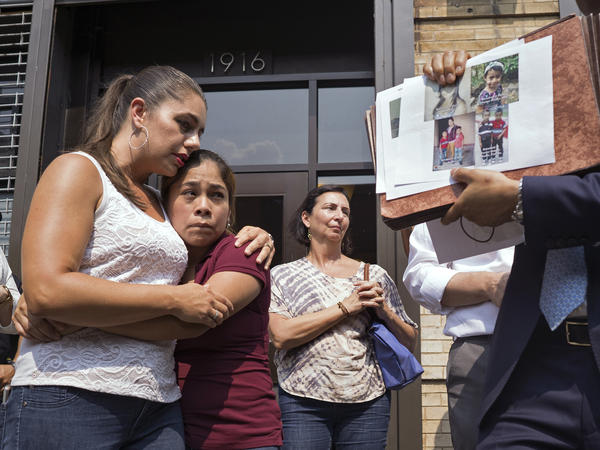 Yeni Gonzalez (center), a Guatemalan mother who was separated from her three children at the U.S.-Mexico border, is embraced by volunteer Janey Pearl Starks as pictures of other children separated from their families are displayed during a news conference on Tuesday in New York City. Gonzalez saw her children in a New York City facility for the first time since mid-May.