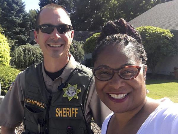 This Tuesday, July 3, 2018 selfie photo provided by Oregon state Rep. Janelle Bynum, shows her posing with a Clackamas County Sheriff's officer after he stopped her in Clackamas, Ore