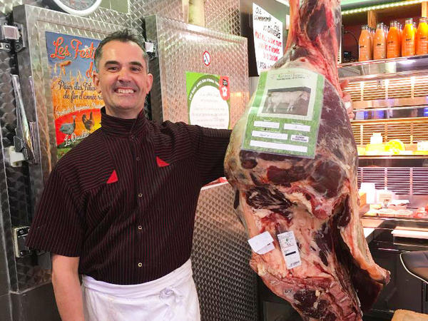 Tass poses with the carcass of a Blonde d'Aquitaine cow. The butcher has papers that include when and where it was born, raised, where it was slaughtered and its vaccinations.