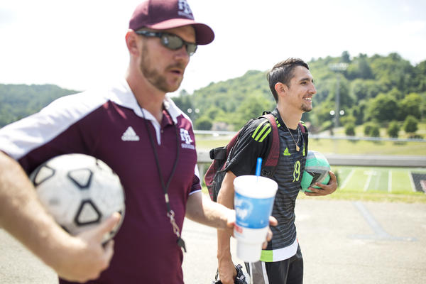 Ricardo Osuna, right, who graduated from high school this spring, and head soccer coach Troy Barkley, left, leave the Galax High School field. Osuna helped to lead the school's soccer team to the state championship title the past two years. Barkley credits the sheer love of soccer that his Hispanic players have as a contributing factor to the team's success.