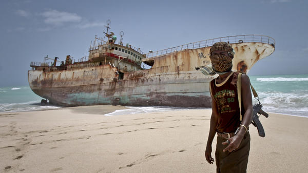 A masked Somali pirate stands near a Taiwanese fishing vessel that washed up in 2012 after the pirates were paid a ransom and released the crew. The image appears on the cover of Michael Scott Moore's new book <em>The Desert and the Sea.</em>
