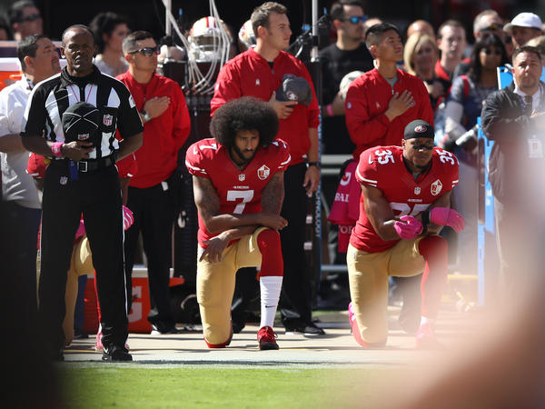 Colin Kaepernick (left) kneels alongside teammate Eric Reid during the national anthem before a game in 2016. Kaepernick initiated a series of protests against police brutality that continue to roil the NFL.