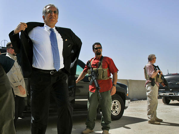 Blackwater security contractors guard Zalmay Khalilzad, then the U.S. ambassador to Iraq, as he arrives at a community sports center in Baghdad in 2006.