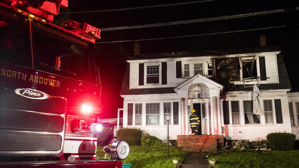 Firefighters inspect a home after gas explosions on Thursday in North Andover, Mass. Gas explosions in three communities north of Boston left multiple homes on fire.