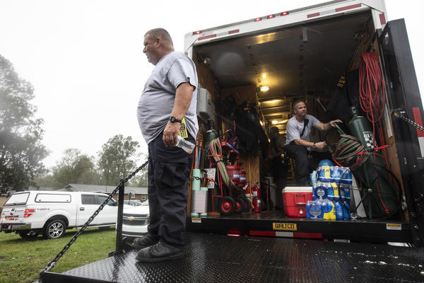 Indiana Task Force One tends to a house on Weaver Street in Wilmington. The slow-moving giant still poses danger to people in North and South Carolina, as its storm surge and intense rains bring high floodwaters to towns both on the coast and inland.