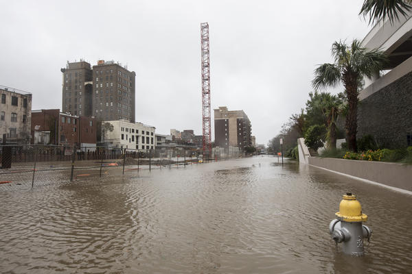 Overflow from the surge of the Cape Fear River along with rain floods downtown Wilmington, N.C. on Friday. Florence's winds have dropped, reducing the hurricane to a tropical storm.