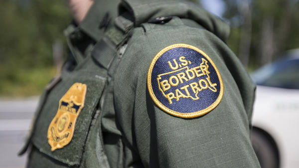 A U.S. Border Patrol agent stands at a highway checkpoint on August 1 in West Enfield, Maine.