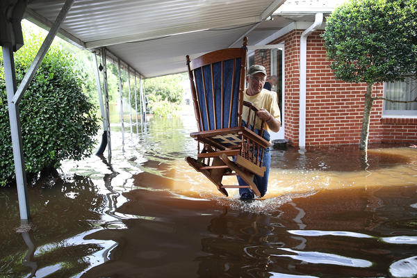 Bob Richling carries items from the home of Iris Darden as floodwater from the Little River starts to seep into her home Monday in Spring Lake, N.C.