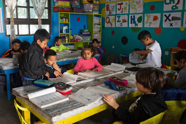 Pre-elementary school children look through workbooks. In Guatemala, where childhood is threatened by poverty, gang violence, drug addiction, and generalized low self-esteem, <em>Los</em> <em>Patojos</em> is seen as a ray of light.