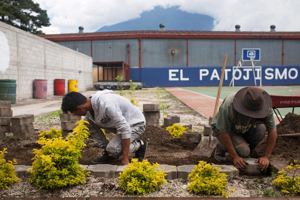 Current students Steven Garcia (left), 16, and Luis Hernandez, 15, help construct around the athletic field in Los Patojos' new campus.