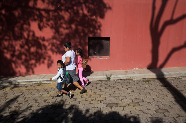 A woman walks two children in Jocotenango.