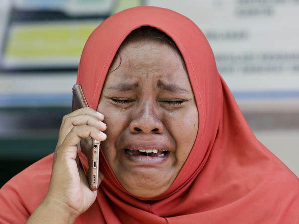 A woman weeps while using the phone of her daughter, who was killed in the 7.5 magnitude earthquake that struck Palu, Indonesia, last week. The mother did not get the chance to see the body of her daughter before she was buried in a mass grave.