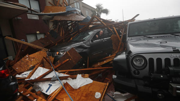 A storm chaser climbs into his vehicle as the eye of Hurricane Michael passes over Panama City Beach, Fla., hoping to retrieve his equipment after a hotel canopy collapsed in the parking area. The storm came ashore as a nearly Category 5 hurricane Wednesday.