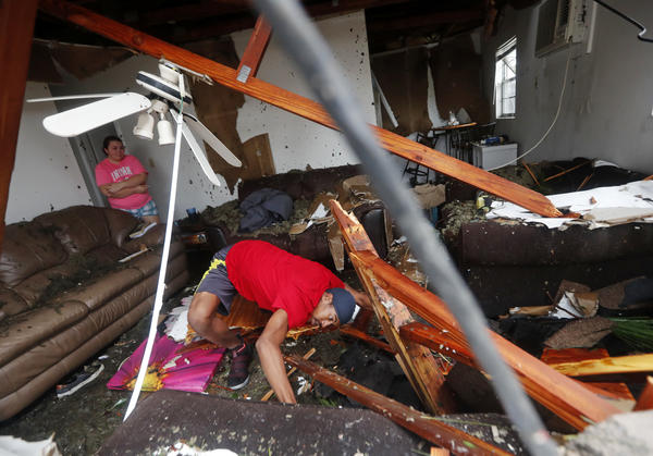 Dorian Carter looks under furniture for a missing cat after several trees fell on their Panama City home during Michael.