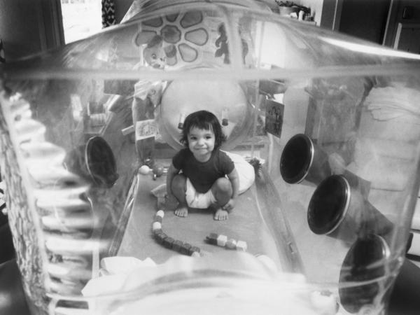 David Vetter plays in the enclosed plastic environment that he had to stay in to survive.