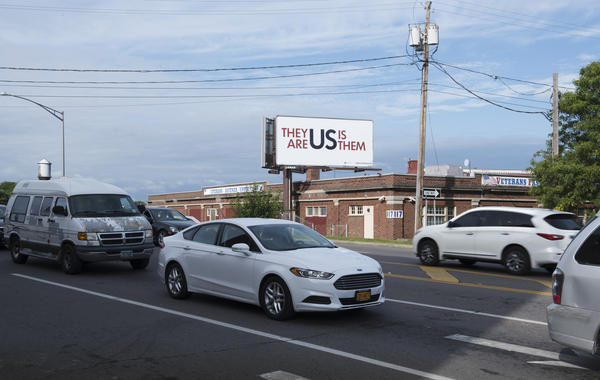 "A billboard created by Hank Willis Thomas in Syracuse, N.Y., says: ""They Are Us,"" and ""Us Is Them. The artist co-founded <a href=""http://forfreedoms.org/"">For Freedoms</a>, a nonpartisan campaign behind the public art project titled The 50 State Initiative."
