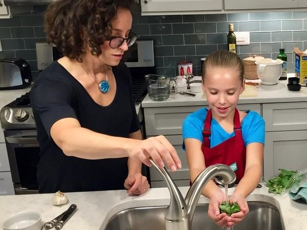 Molly Birnbaum, <em>America's Test Kitchen Kids</em> editor in chief, helps 8-year-old Lucy Gray make a one-pot pasta meal from a recipe in the new book, <em>The Complete Cookbook for Young Chefs</em>.