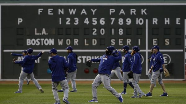 Bundled-up members of the Los Angeles Dodgers practice Tuesday at Fenway Park in Boston for Game 1 of the World Series against the Boston Red Sox. Temperatures are expected to drop into the low 40s tonight, and thunderstorms are possible.