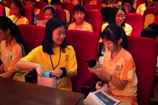 """Ethnic Chinese students from the U.S. and Indonesia exchange gifts with local students during a """"roots-tracing"""" trip in Taishan."""