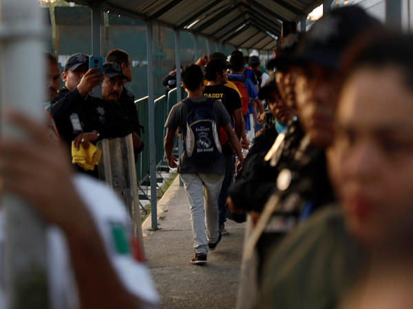 Central American migrants, part of a caravan trying to reach the U.S., cross from Guatemala into a Mexican border and customs facility in Ciudad Hidalgo, Chiapas, on Wednesday.