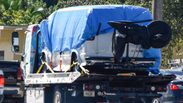 A van covered in blue tarp is towed by FBI investigators on Friday, in Plantation, Fla., in connection with the pipe bombs  mailed to top Democrats.
