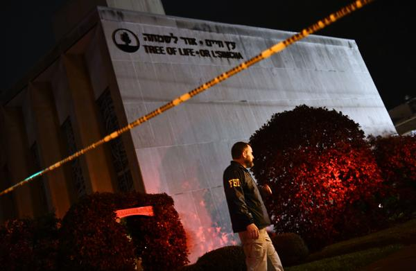 An FBI agent stands behind a police cordon outside the Tree of Life Synagogue after a shooting there left 11 people dead in the Squirrel Hill neighborhood.