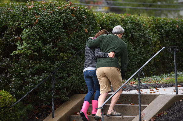 Neighbors around the corner from the site of a mass shooting at the Tree of Life Synagogue embrace one another.