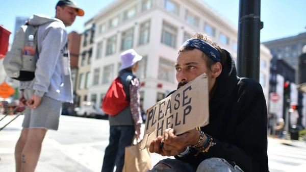 A man panhandles along a sidewalk in downtown San Francisco, California on Tuesday, June, 28, 2016.