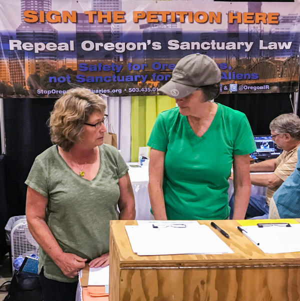 Cynthia Kendoll, left, talks with volunteers at the Oregon State Fair booth of Oregonians for Immigration Reform last year. The group gathered signatures to get Measure 105 on this November's ballot. If passed, the measure would repeal Oregon's 31-year-old sanctuary law.