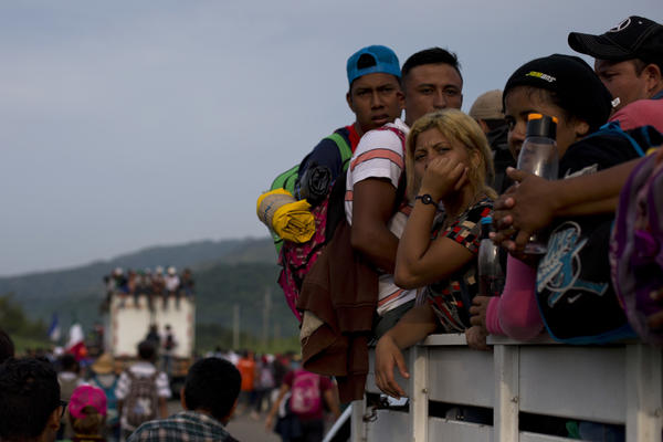 Migrants hitch rides on passing truck as they continue on their journey after Mexican police briefly blockaded the road to keep them from advancing, outside the town of Arriaga, Mexico, Saturday, Oct. 27, 2018. Hundreds of Mexican federal officers carrying plastic shields briefly blocked the caravan of Central American migrants from continuing toward the United States, after several thousand of the migrants turned down the chance to apply for refugee status and obtain a Mexican offer of benefits. (AP Photo/Rebecca Blackwell)