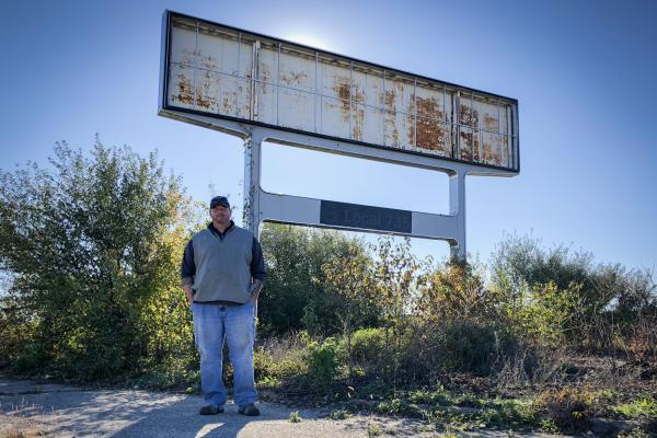 Don Skidmore stands in front of a sign for United Auto Workers Local 735, the union chapter he represented as president when he was a General Motors employee.