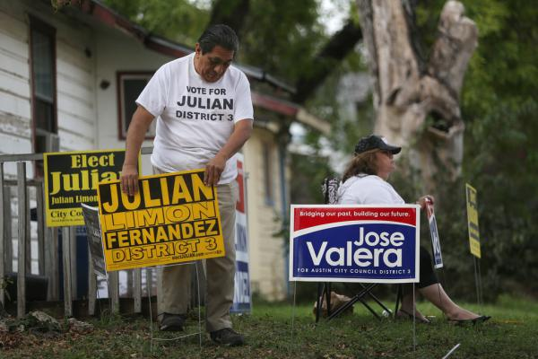 Gavino Fernandez Jr. puts campaign signs in the front yard of his East Austin home after asking Peggy Vasquez (seated) to remove the signs that she posted for an opposing candidate.